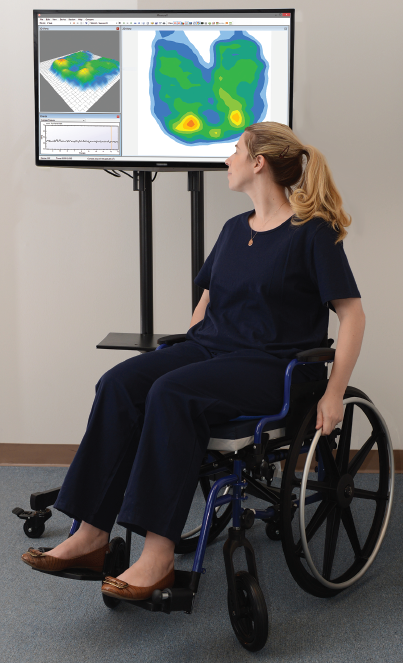 A woman in a wheelchair observes a digital pressure map image.
