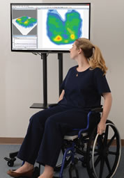 A woman seated in a wheelchair observes a pressure mapping display.